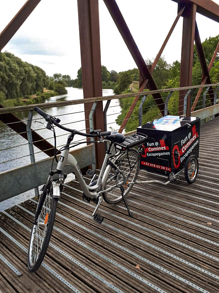 Bicycle and attached escape game equipment box atop a bridge outdoors in Comines-Warneton