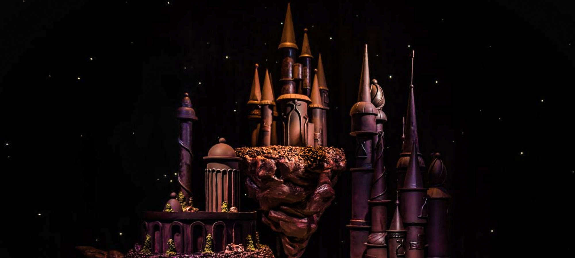 Chocolate castle sculpture with multiple towers and spires on display in a dark room in Chocolate Nation, Antwerp