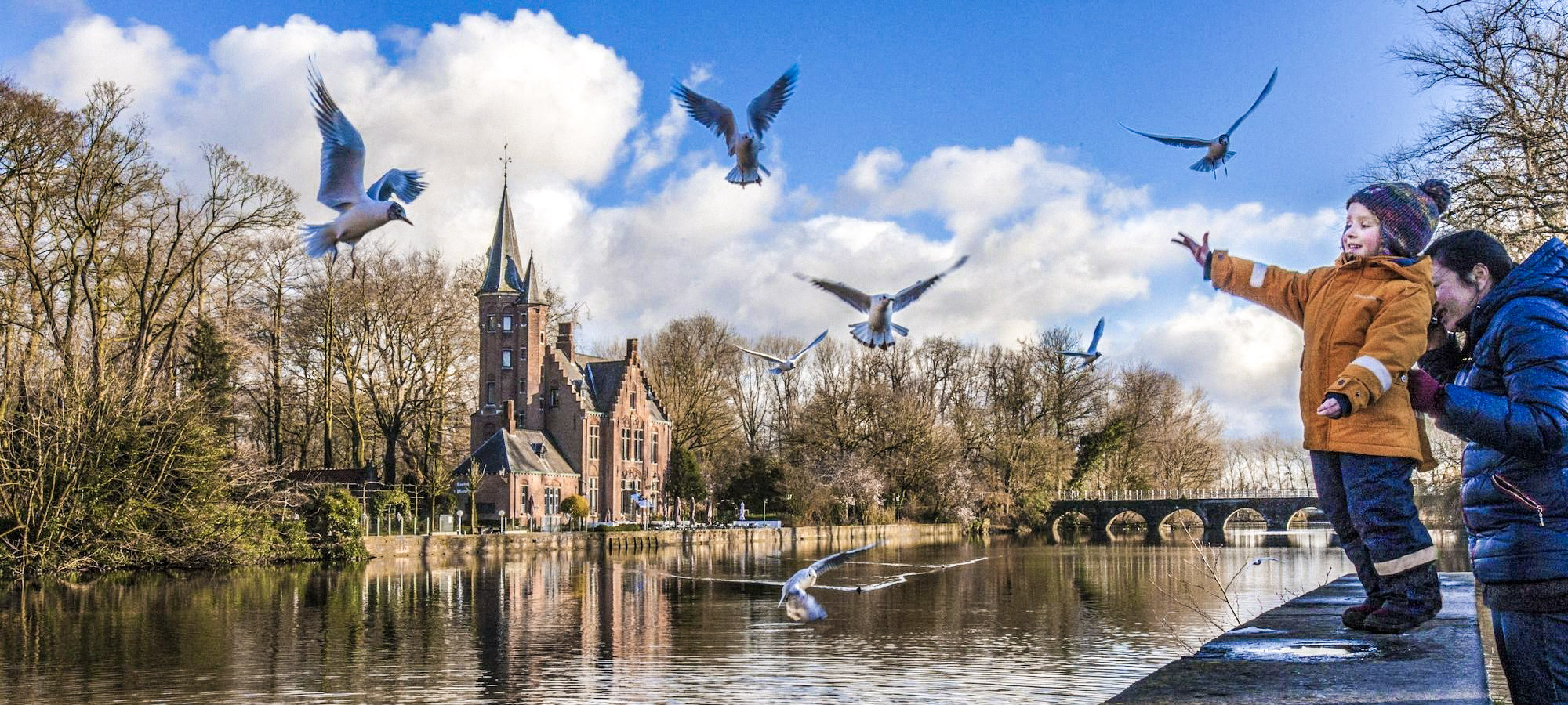 Child and mother looking at the birds at Minnewaterpark, Bruges, Belgium