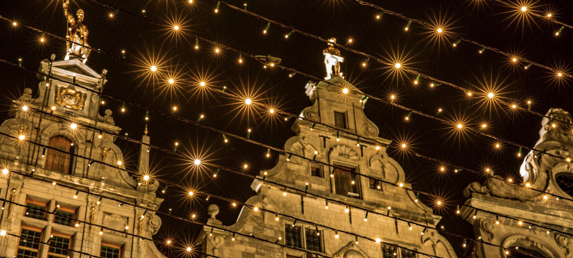 Christmas lights canopy strings hanging above the Grote Markt by the guild halls at night, Antwerp, Belgium