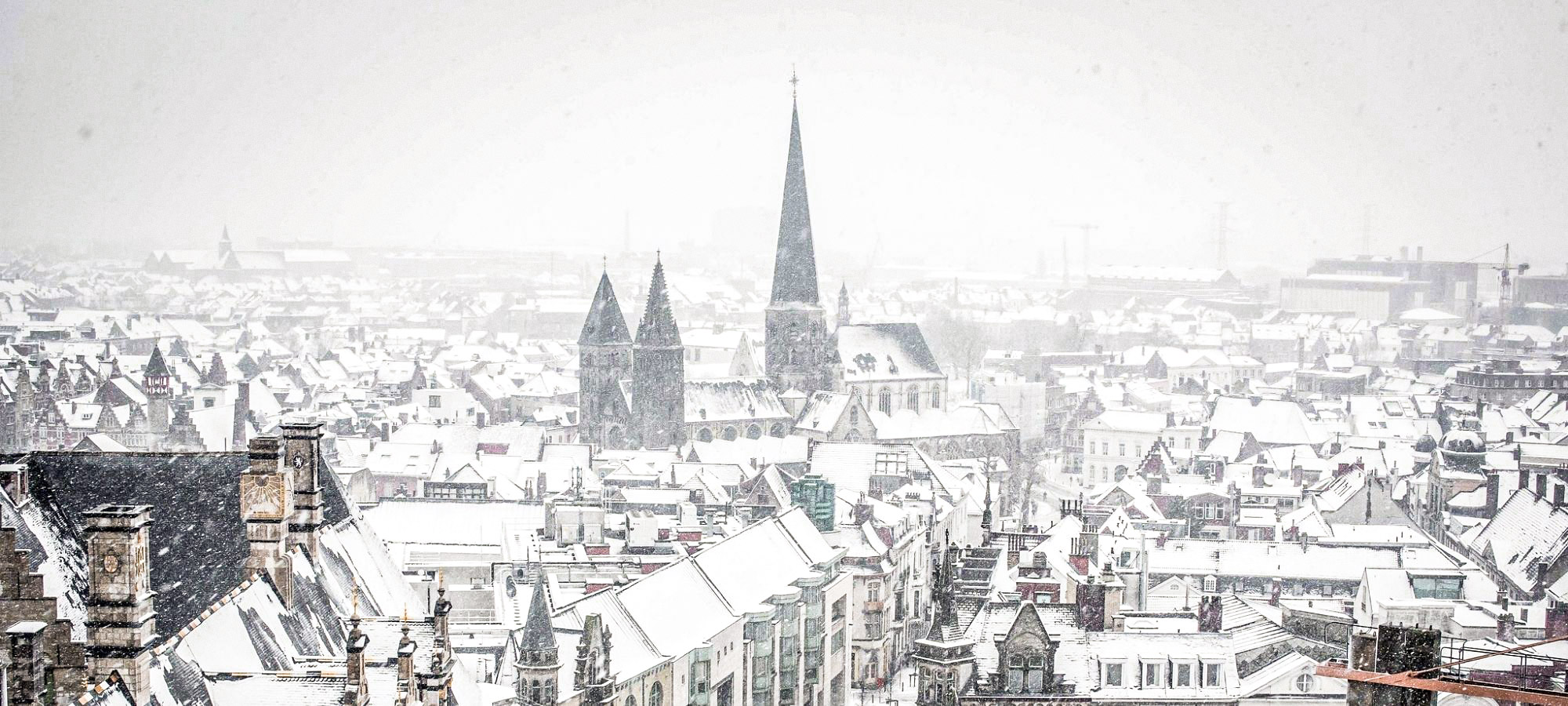 Snow over the city, St Nicholas Church, and dragon belfry in Gent, Belgium