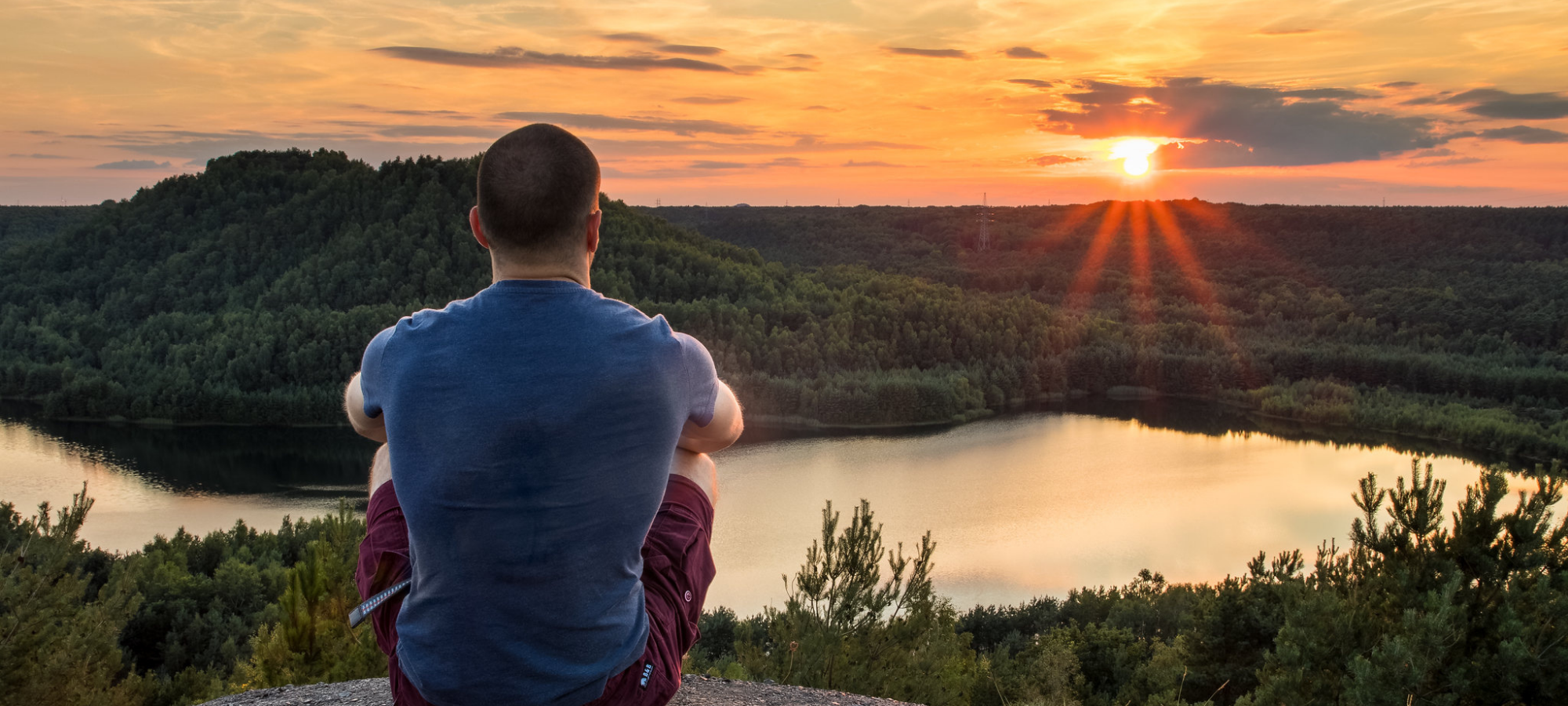 A man watching the sunset on top of a Terrill at Connecterra, part of the Hoge Kempen National Park in Limburg, Belgium