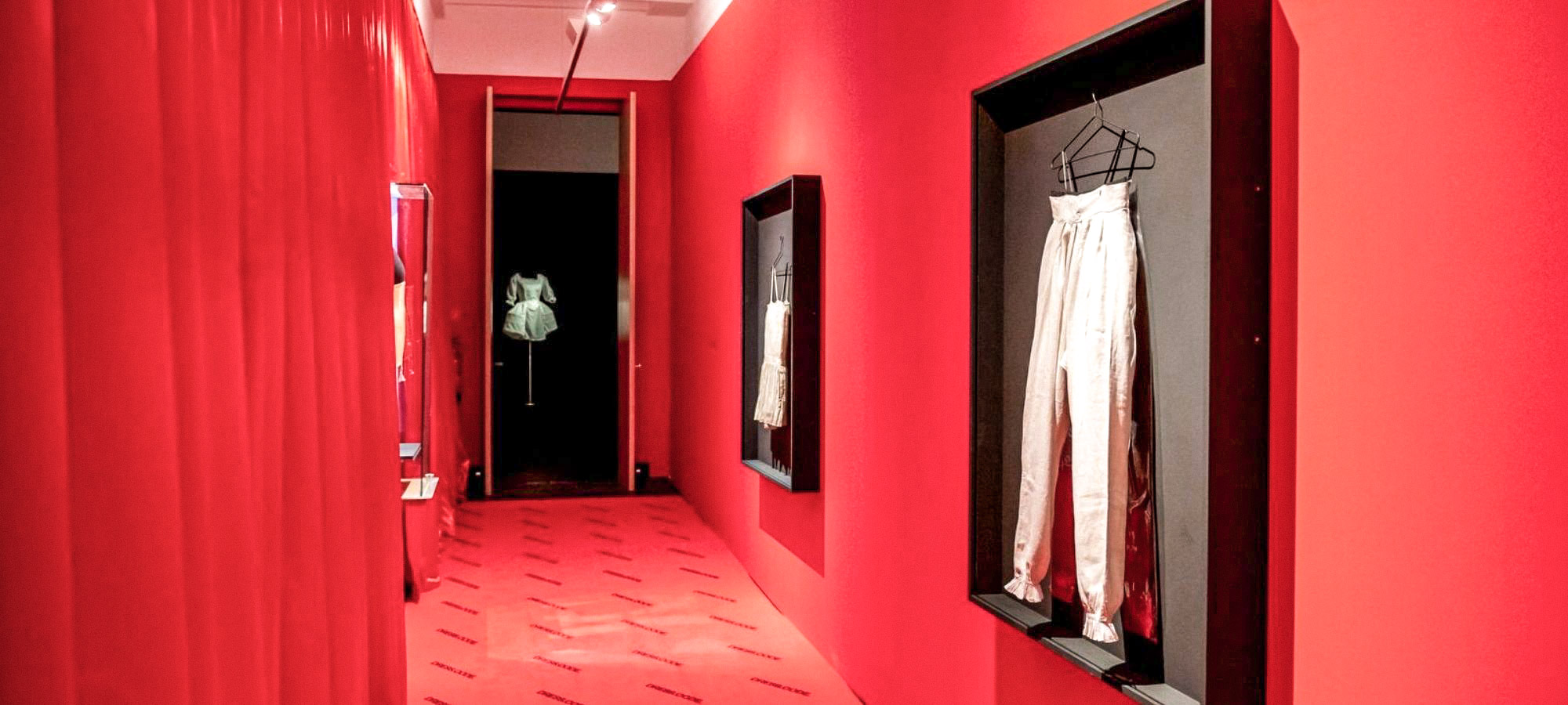 A pair of old, white trousers are hung on the wall of a red corridor in a black frame