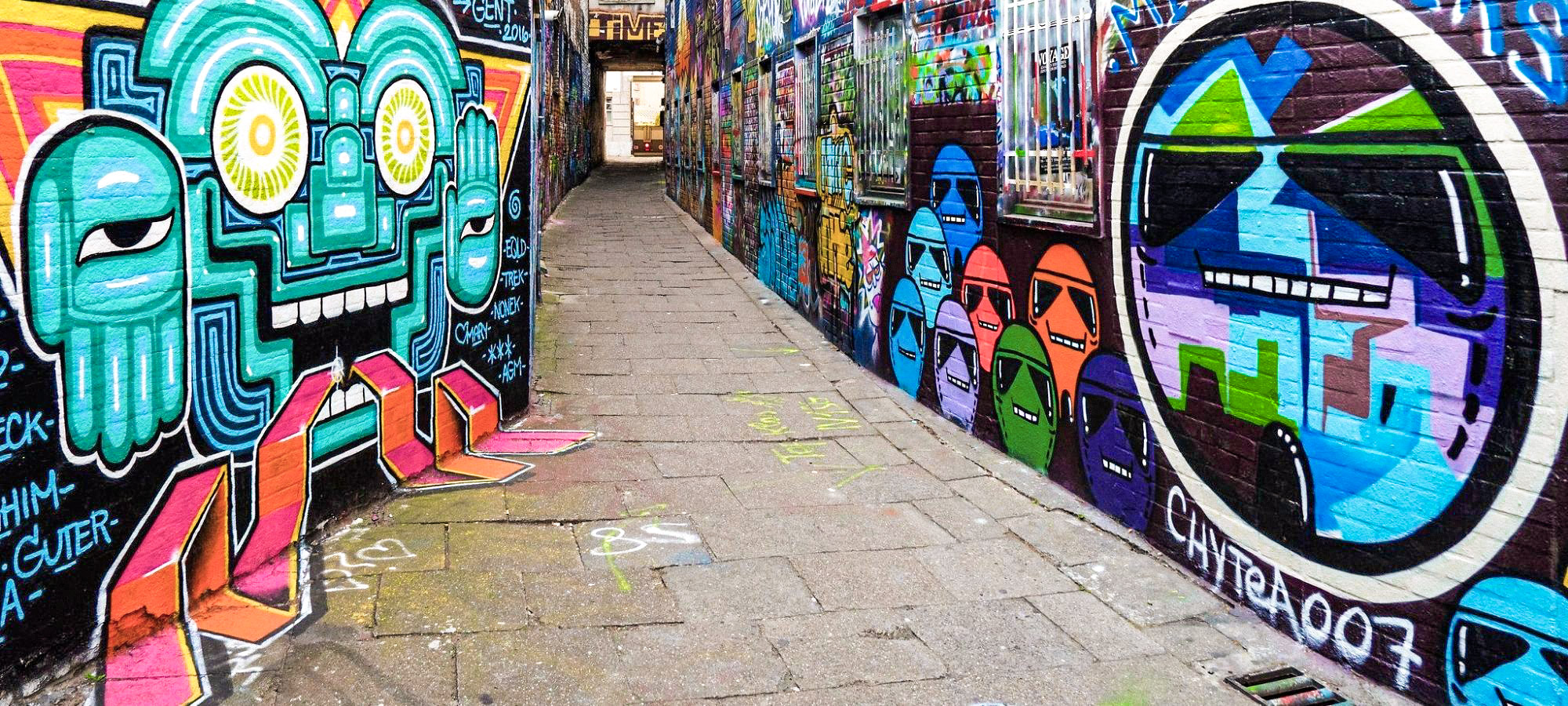 Colourful, futuristic graffiti is painted along the side of the walls of a thin alley