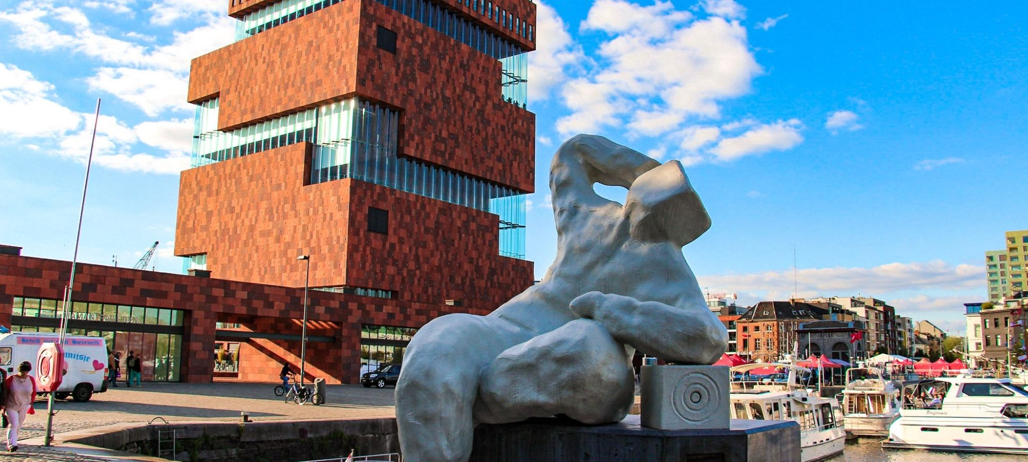 """""""The Antwerp Whisperer"""" sculpture by Daisy Boman of a white human figure with a box for a head near the dock and MAS, Antwerp"""