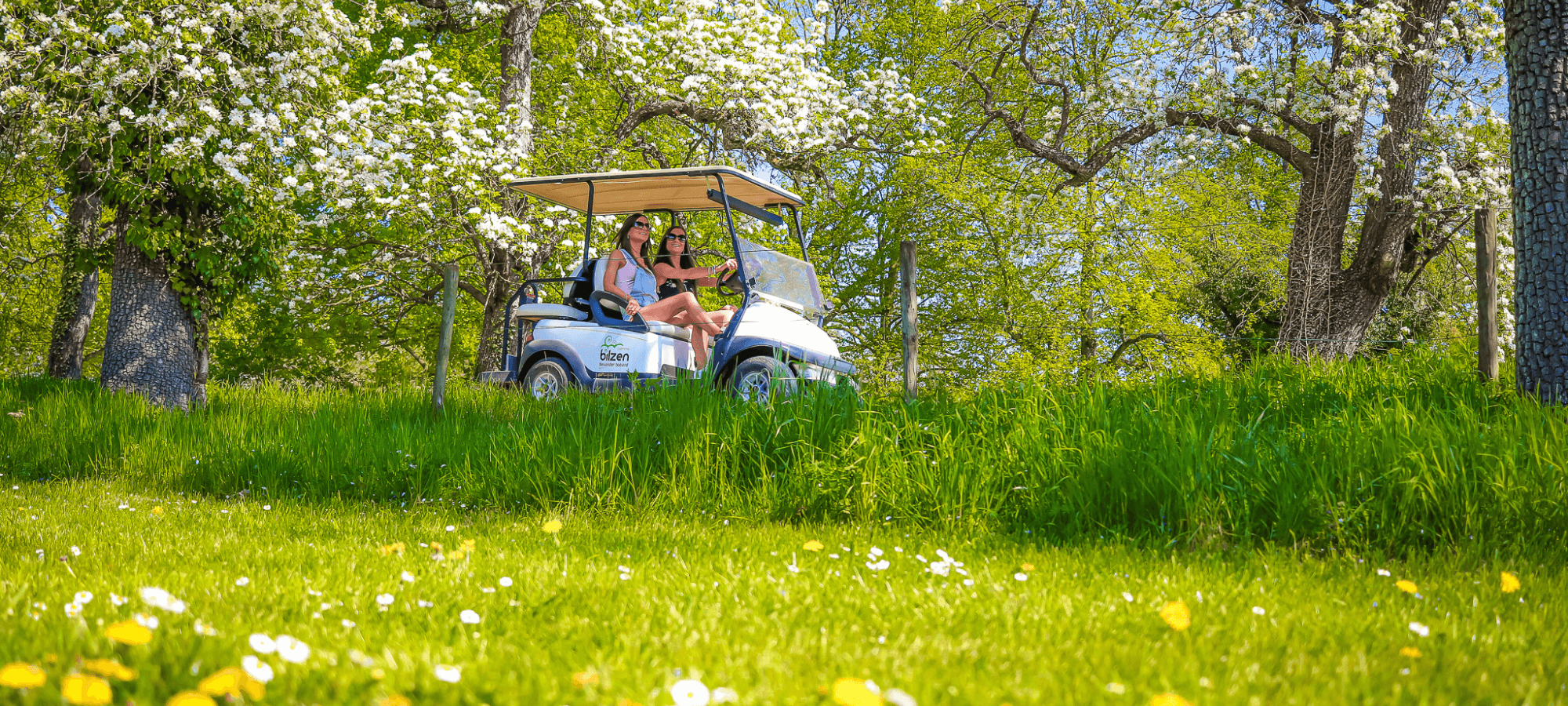 Two women riding an electric golf cart in the Belgian countryside