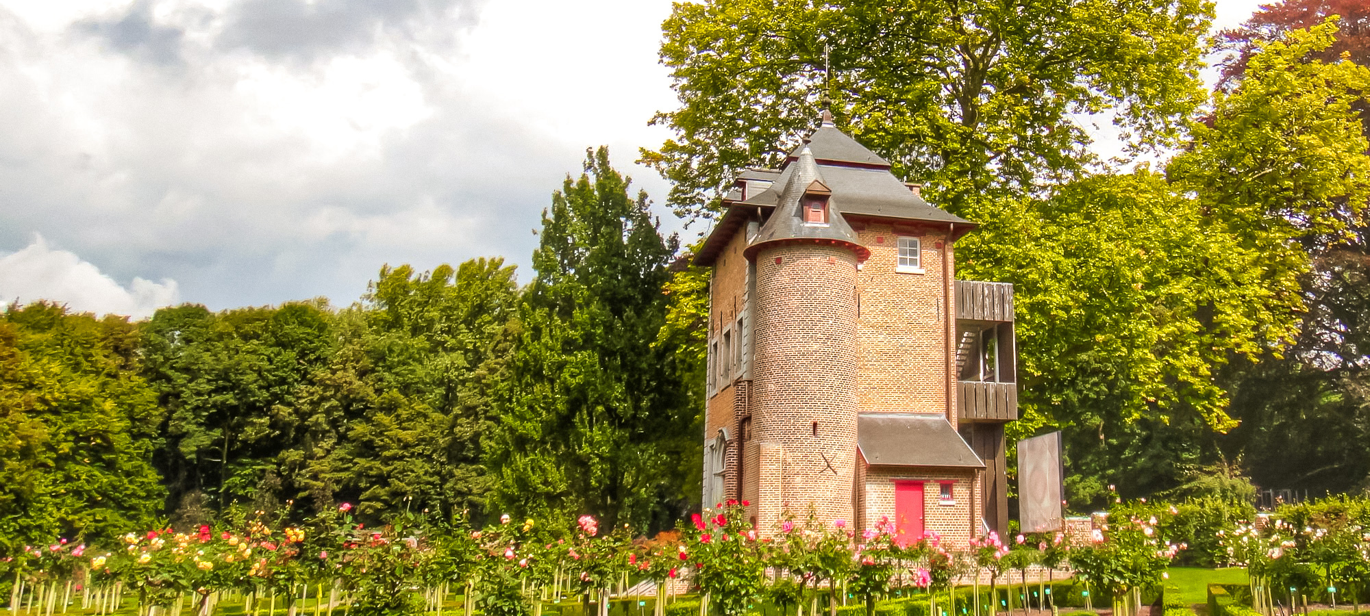 A smart brick building with a turret behind a row of rose buses at Coloma Rose Garden, Belgium