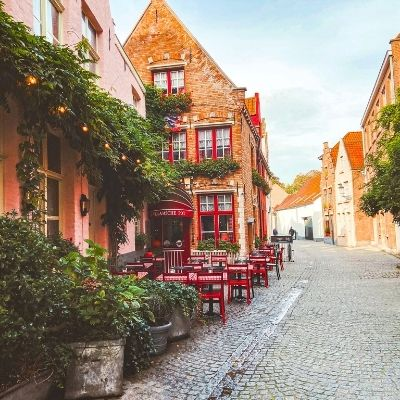 Red outdoor seating on a street in Bruges, Belgium