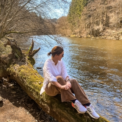 Woman sitting on a log by the river on the Le Herou hike.