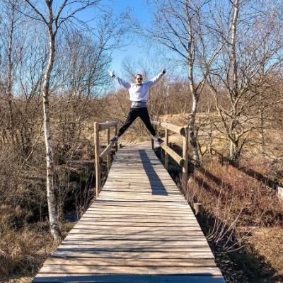 Woman jumping on a wooden bridge, Belgium