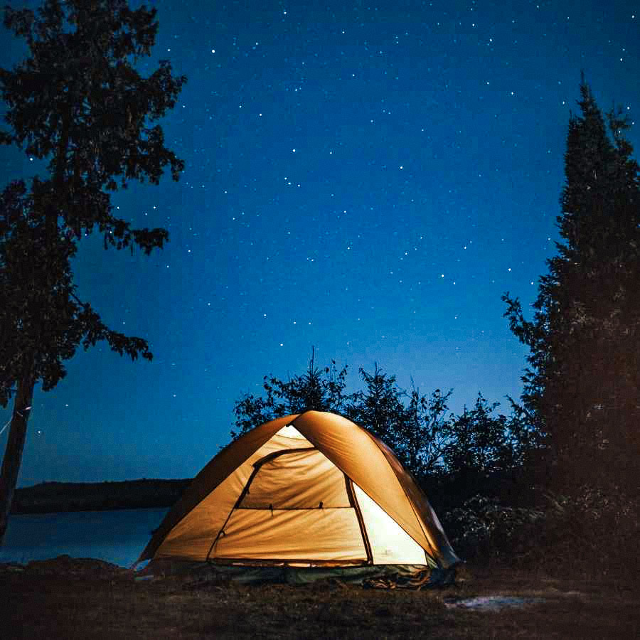 Camping outdoors at night under the stars