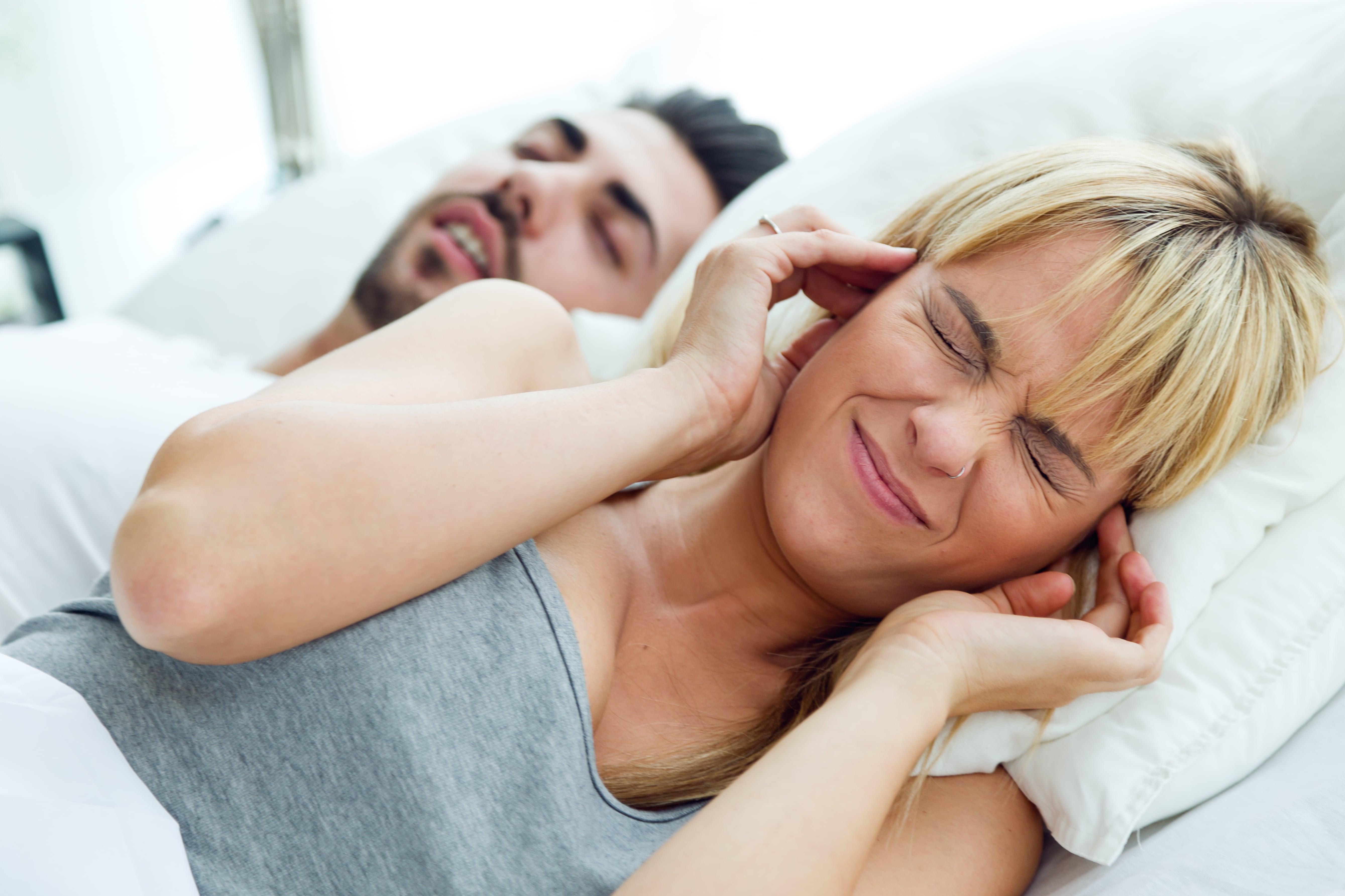 Un couple au lit, la femme se bouche les oreilles car l'homme ronfle.