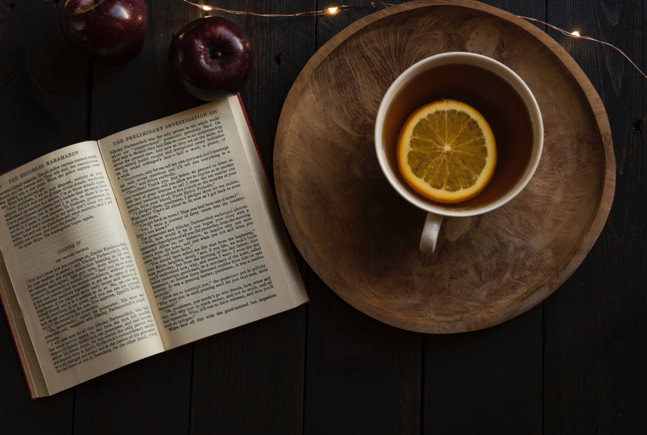 Visuel relaxant : un livre ouvert, une tisane au citron et quelques pommes.