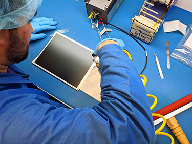 A technician repairing an LCD in the warehouse