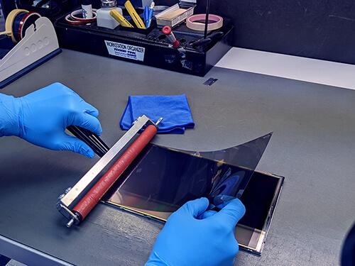 technician adding lcd polarizer film to display