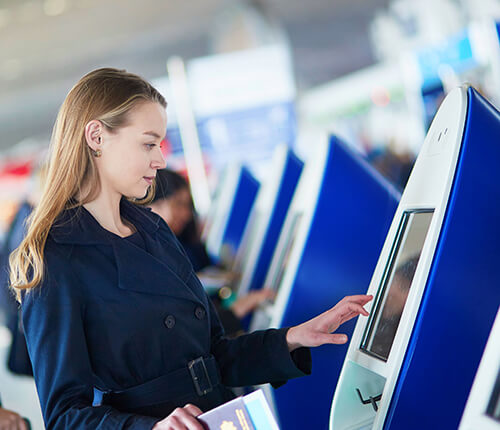 woman at mall kiosk checking out with shopping bags