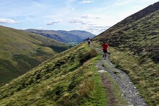 photo of runners on a mountain trail