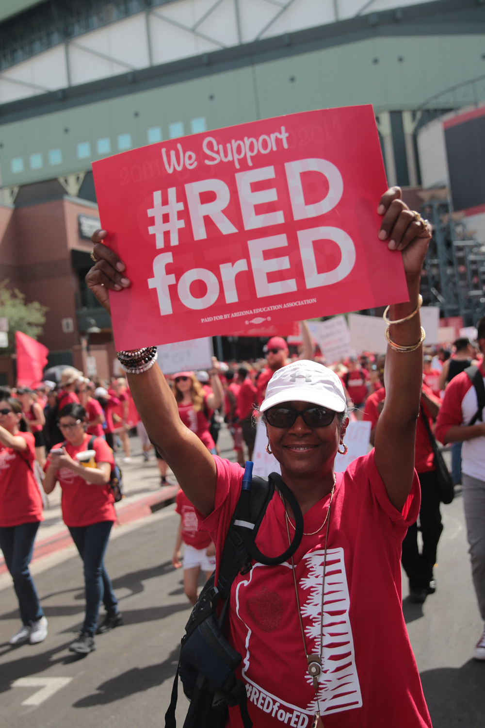 """Woman at a rally carrying a sign that says """"We Support #RED for ED"""""""