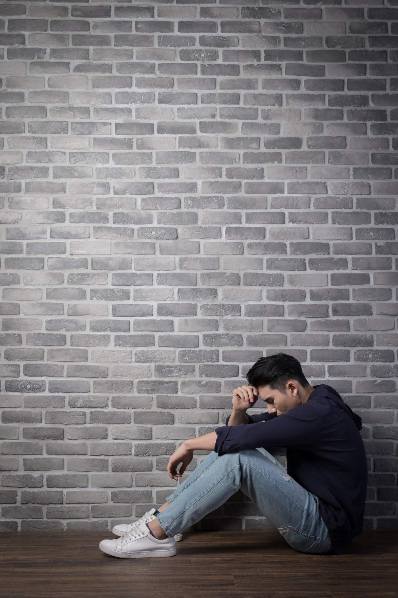 man experiencing sadness with brick background
