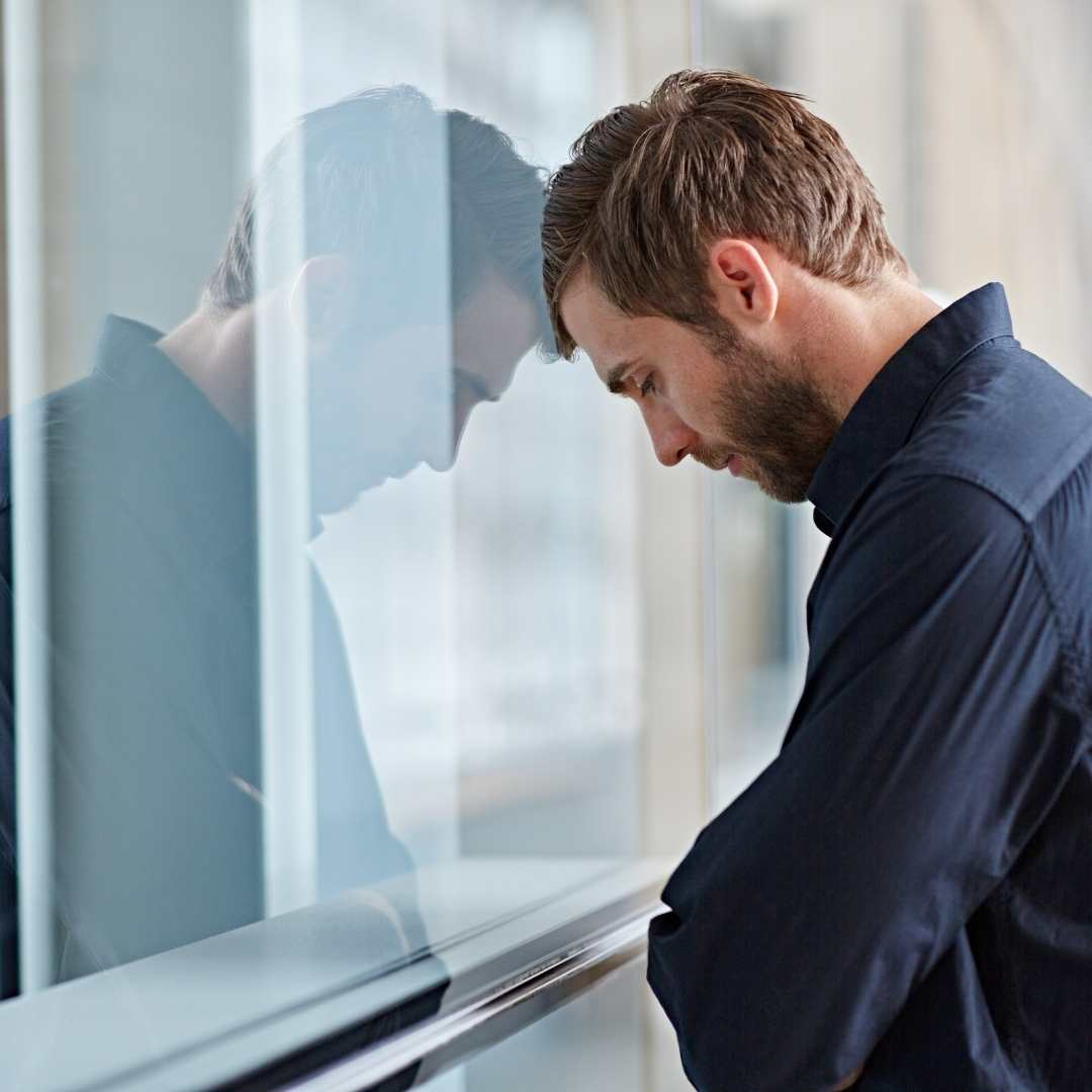 man experiencing depression and looking into window