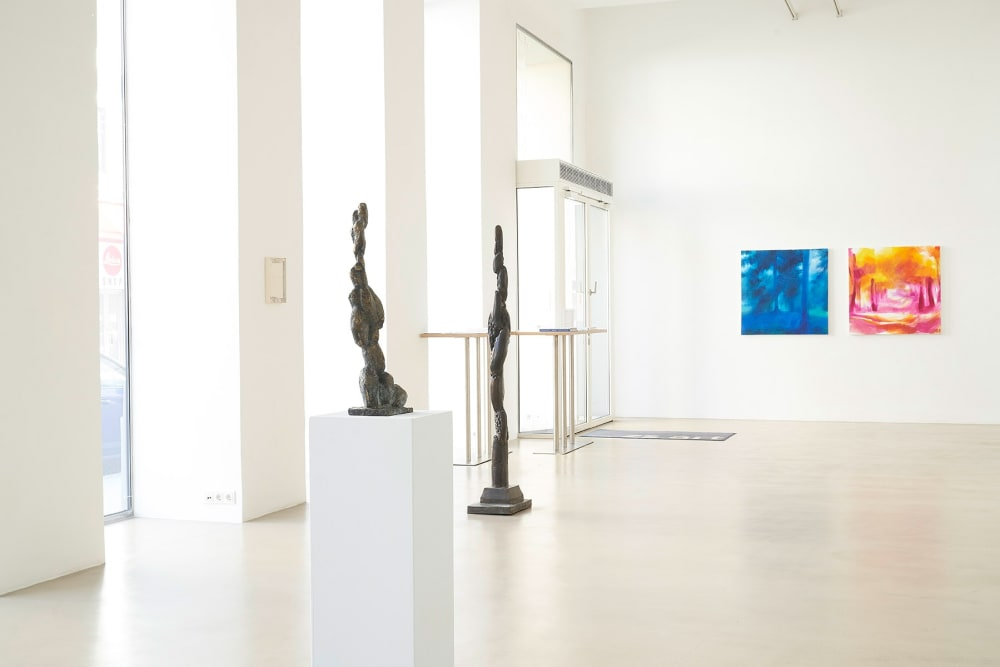 ZS Art Gallery shows the gallery space with high white walls and high windows showing paintings and sculptures