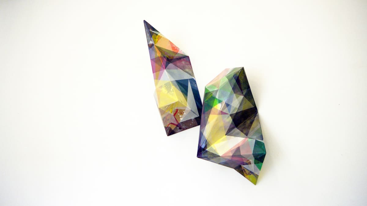Artwork show a razzle dazzle multi-colored sculpture hanging from the wall