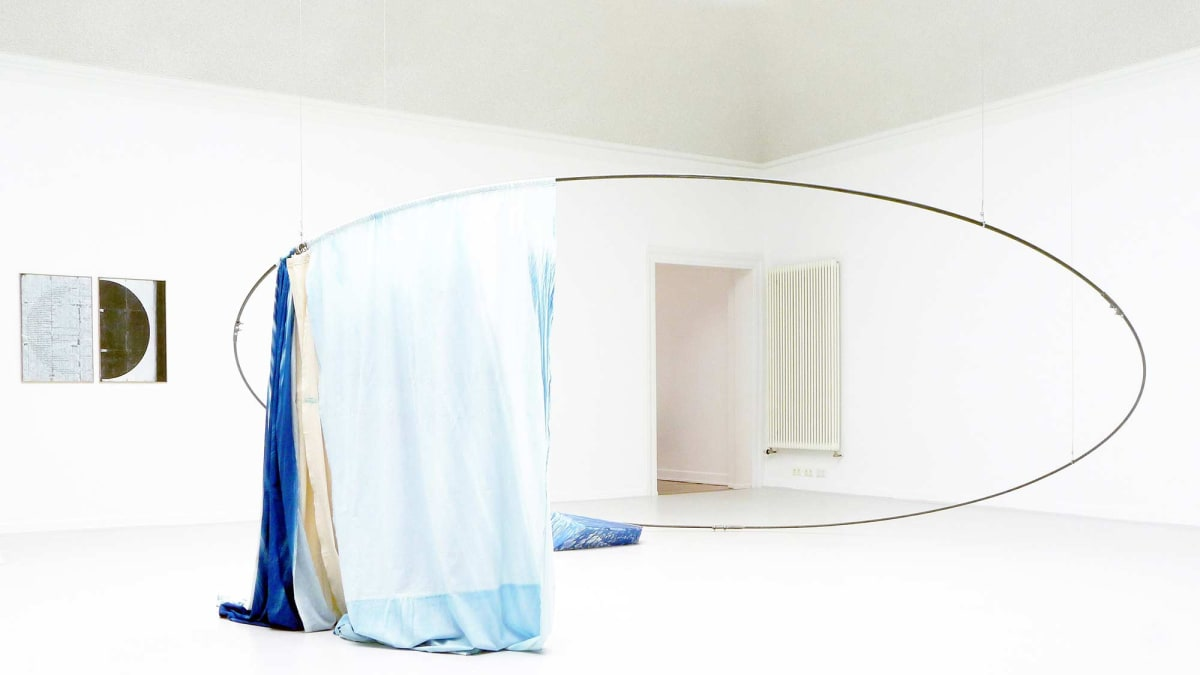 kunstverein konstanz present the artists irena eden stijn lernout the image shows a white room  with a large circular object semi in the air with light blue and dark blue like curtains