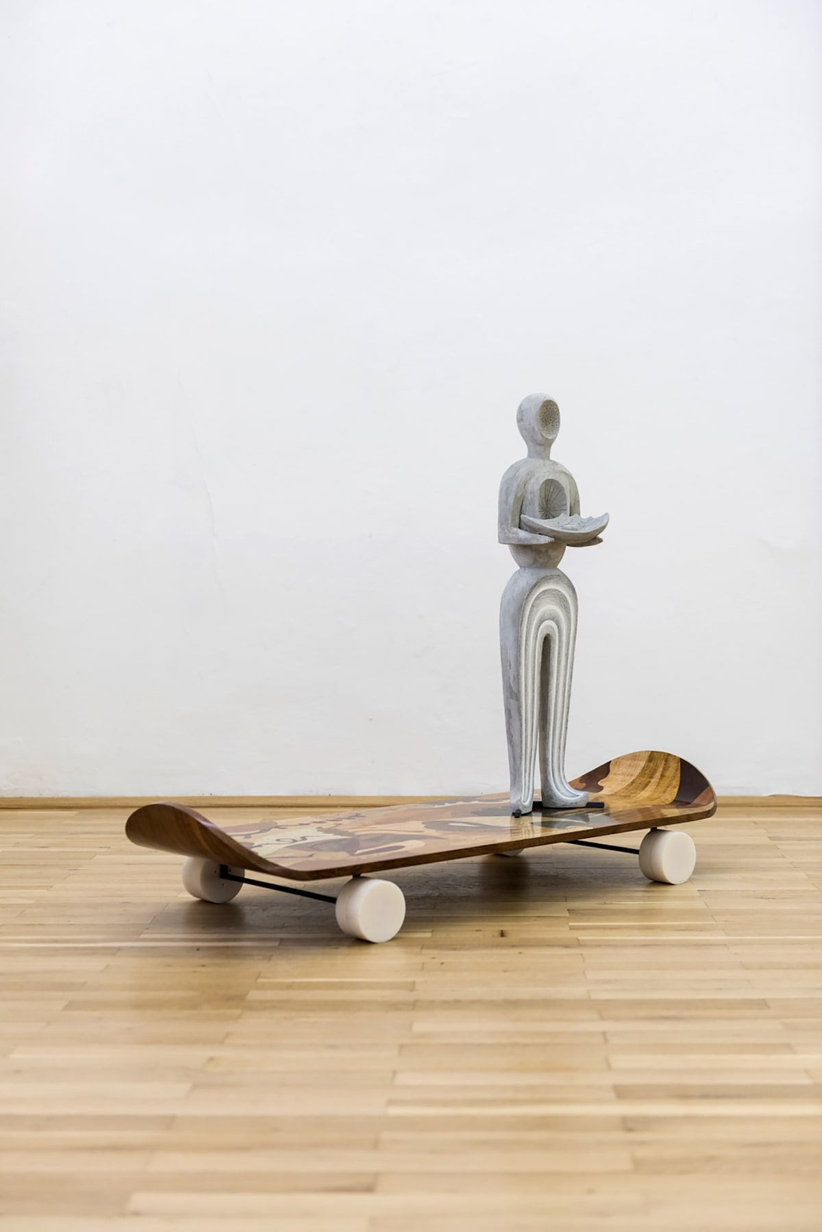 Image shows a sculpture standing on a wooden skateboard