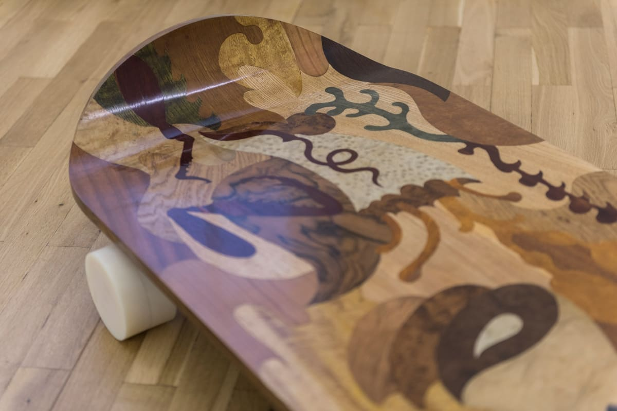 Image shows close up of a scateboard made up of different wood colorings showing natural forms