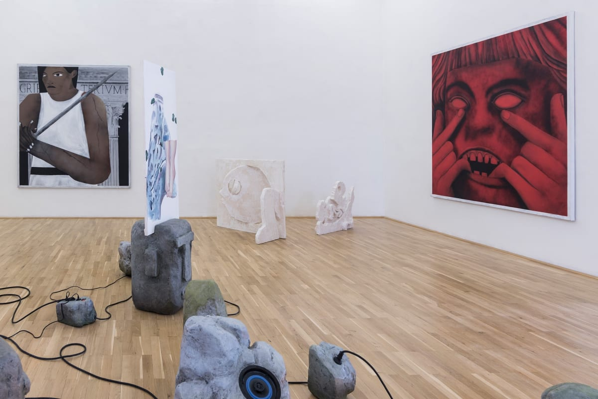 the image shows a room in the gallery with large paintings one of a woman and one of a scary red head. On the floor there is an installation of historic looking heads.