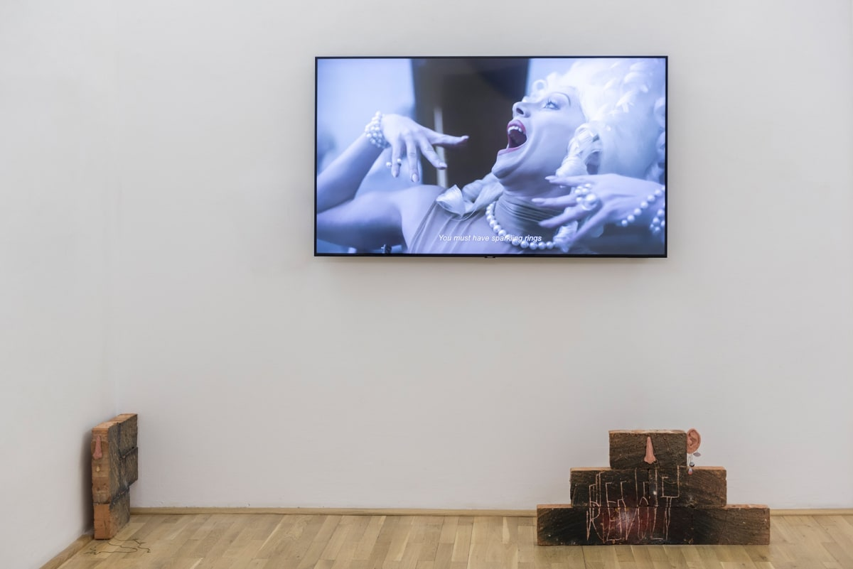 Image shows a video installation as well as 2 smaller brick sculptures on the floor