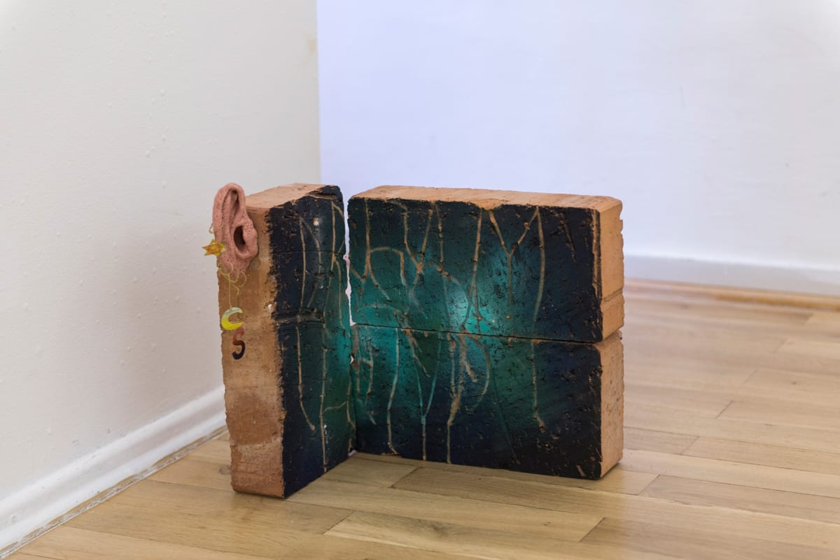 Image of a sculpture. Bricks painted on in a very dark green color and scratches on the surface