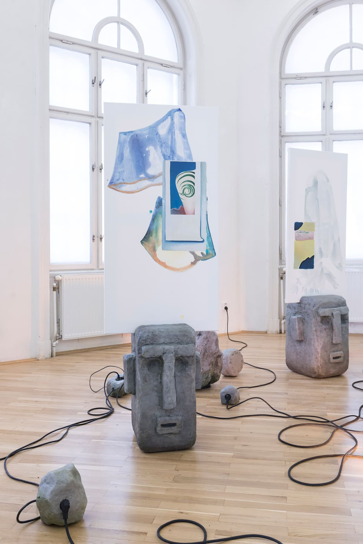 Image shows a gallery room with installations on the floor, cables, paintings on material hanging from the ceiling