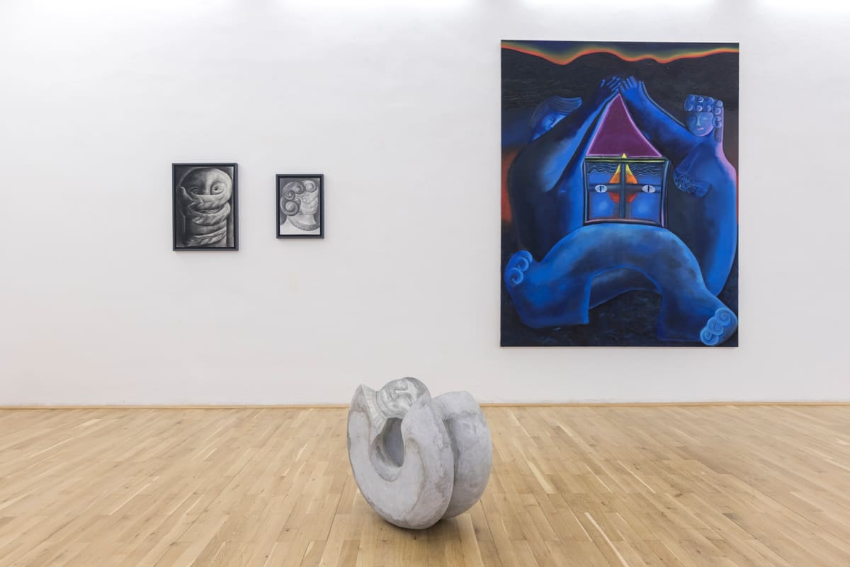 View of a room with a large blue painting, two smaller black and white drawings and a stone sculpture on the floor