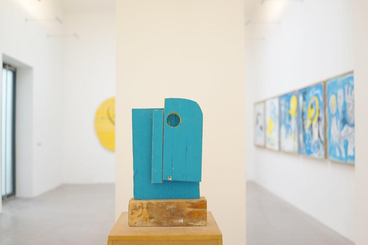 ernst koslitsch raum mit licht exhibition showing the venue artworks and a blue wooden sculpture on wooden unpainted blocks.