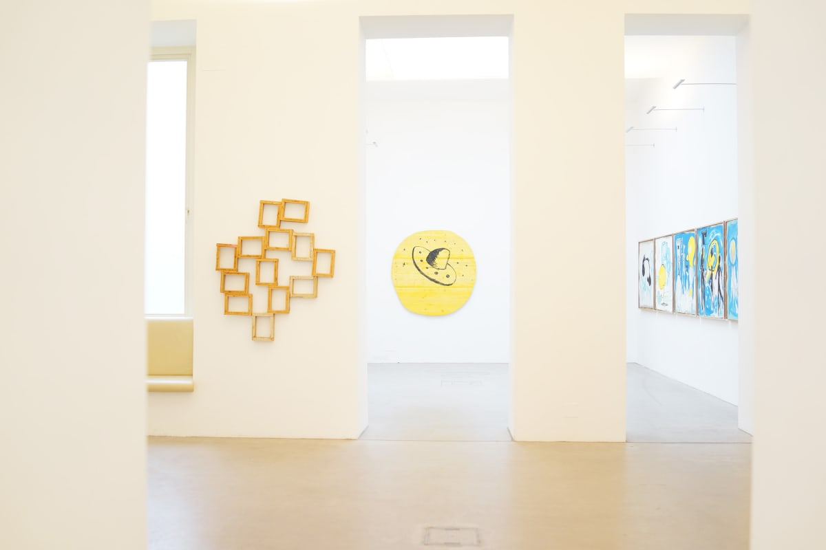 ernst koslitsch exhibition we have to move the island shows the gallery raum mit licht with 2 scultures in yellow wood, one with a large sombrero looking ufo and three paintings in the very back