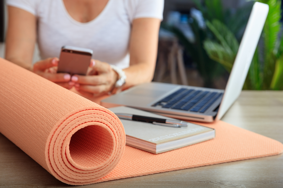 Yoga business owner sitting at her desk with pen-paper, laptop and a rolled up yoga mat