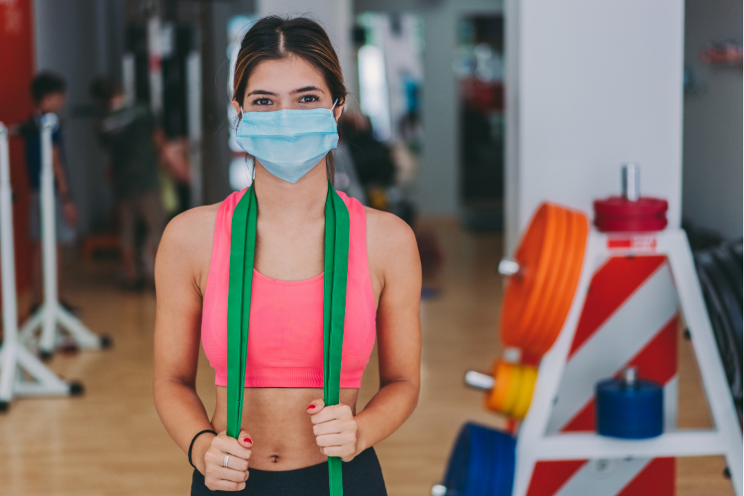 A fit lady wearing a mask and standing in a gym with a resistance band around her neck