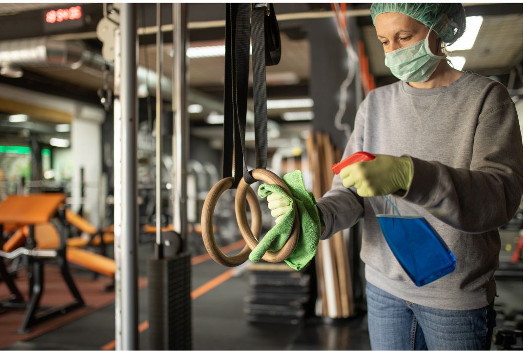 Woman wearing gloves and safety mask, sanitizing gym equipment using disinfectant