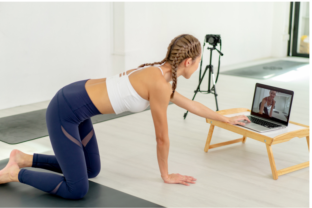 Women with proper live-streaming set-up and digital camera about to start a yoga classs