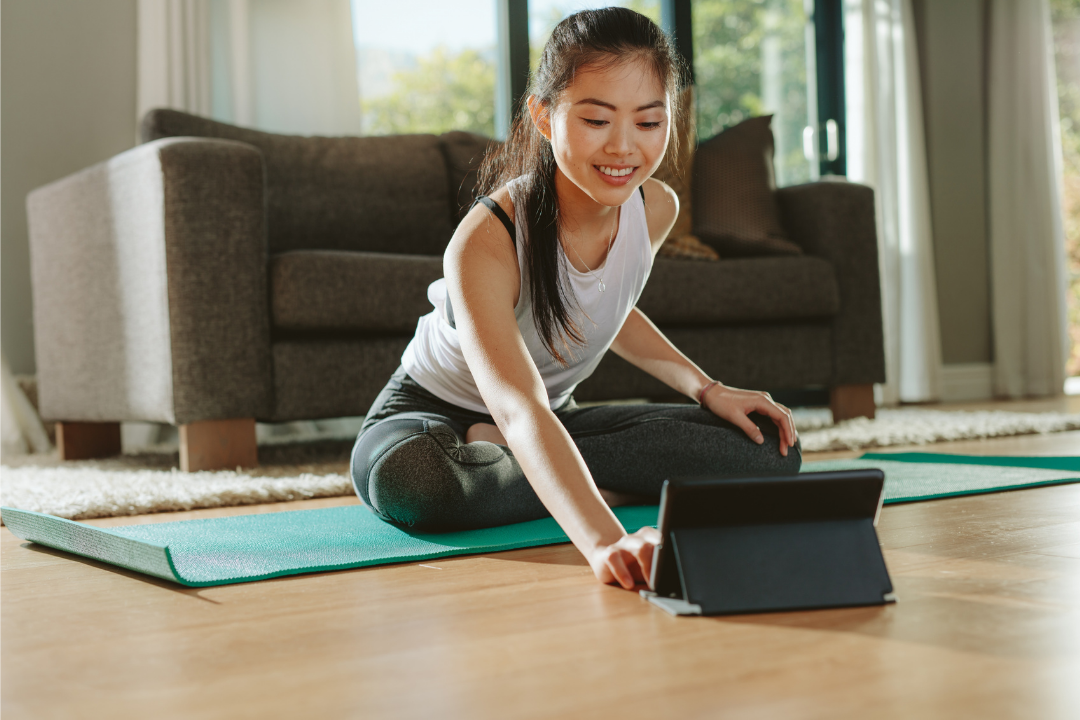 Women touching her i-pad to join a yoga class while sitting on her yoga mat