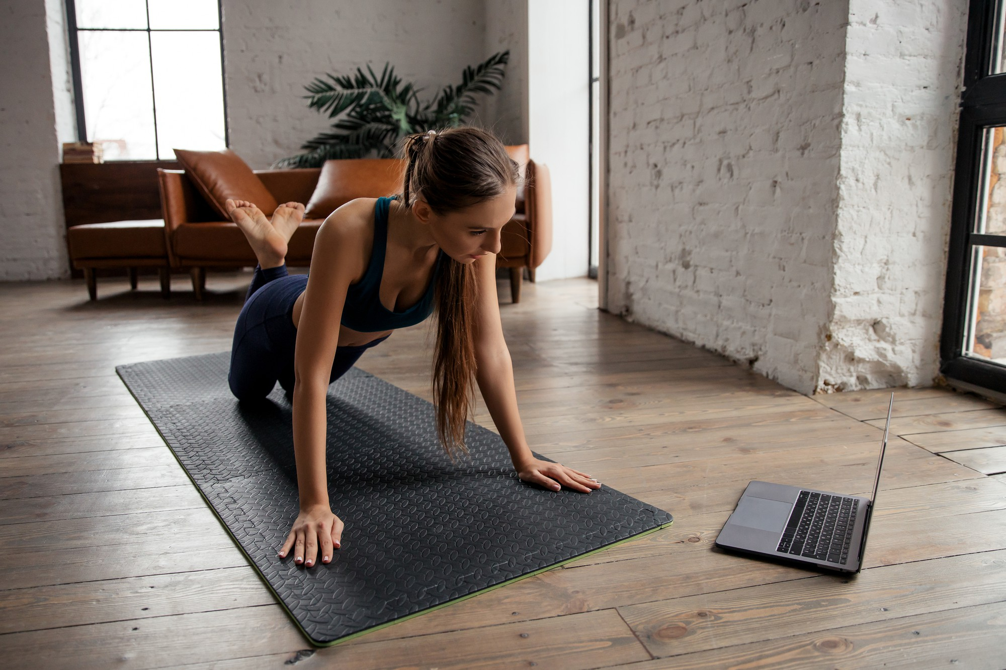 Women performing a yoga asana and live-streaming it through her laptop