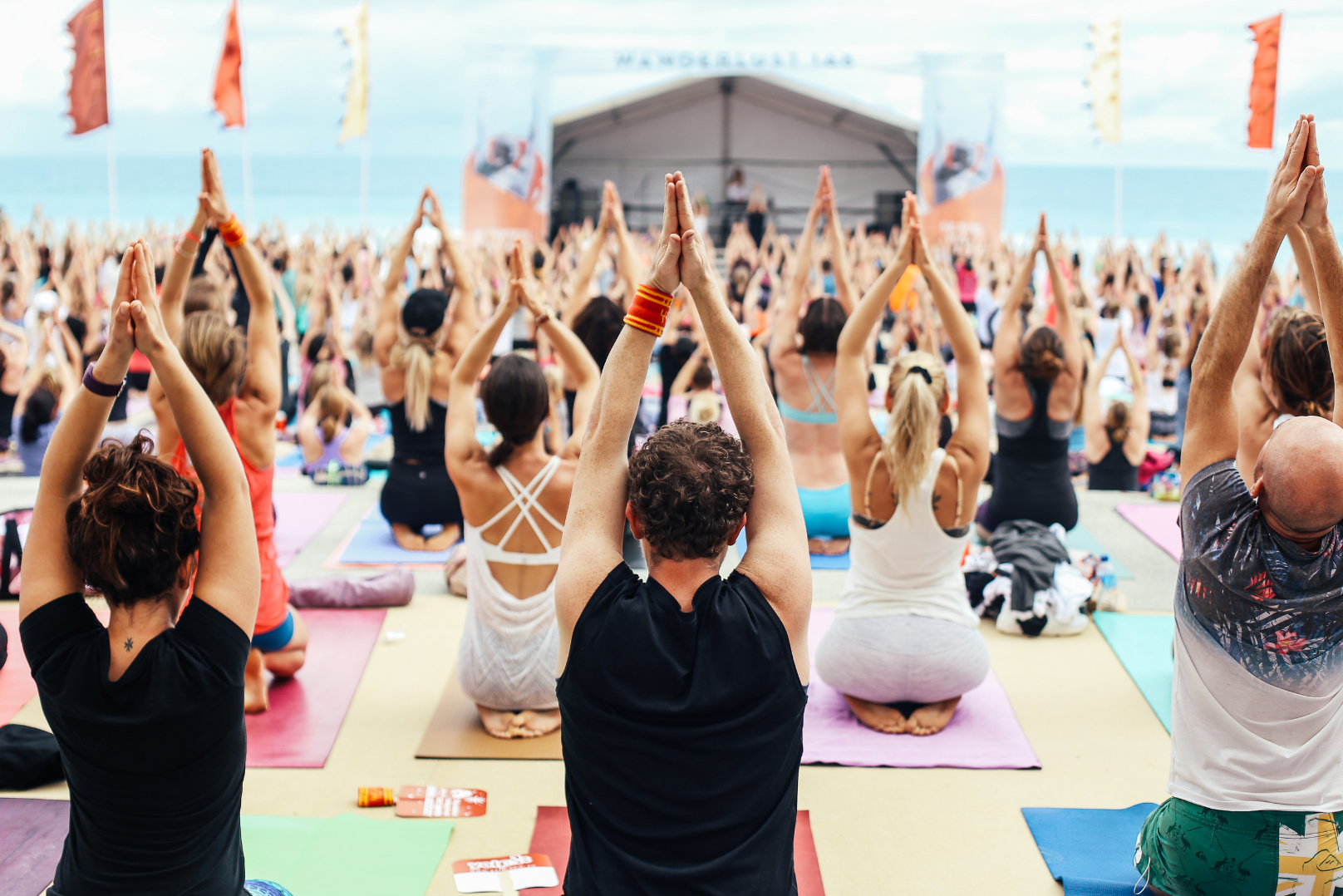 A yoga workshop with several people folding hands above their head
