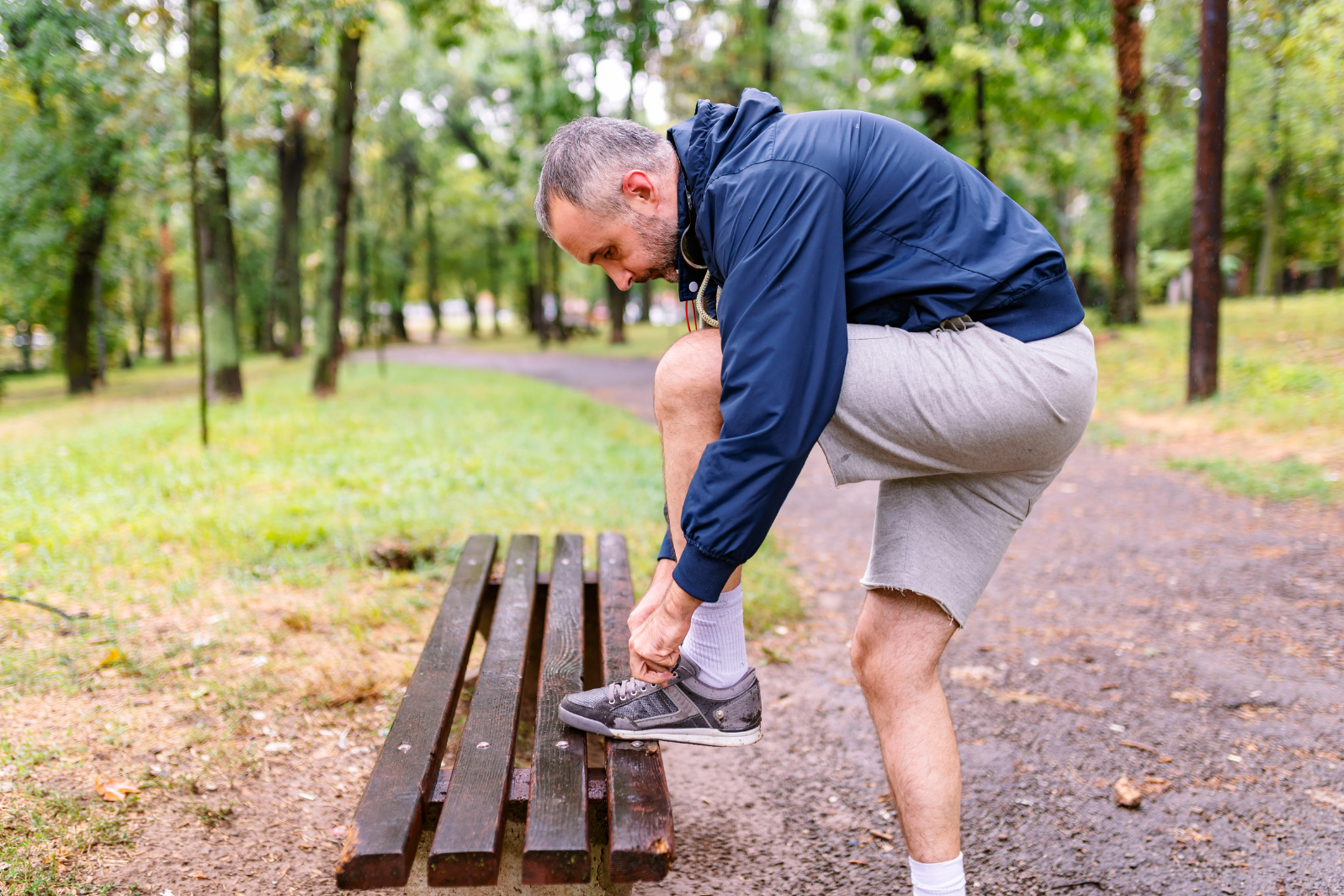Man in his 40s tying up his laces for a run in the woods
