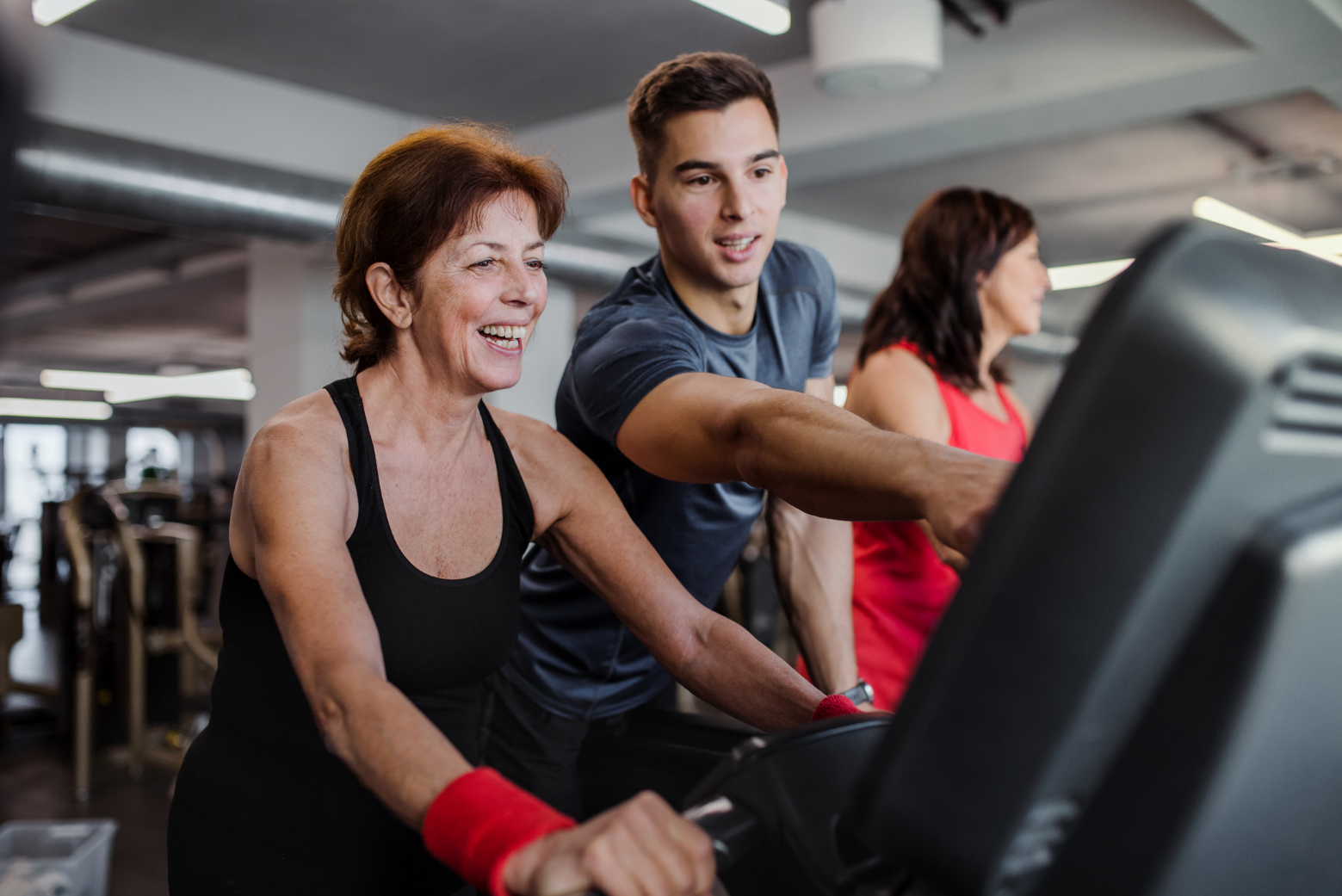 A young male fitness instructor guiding a senior citiA young male fitness instructor guiding a senior citizen woman as she cycles on a gym spin-cyclezen woman as she cycles on a gym spin-cycle
