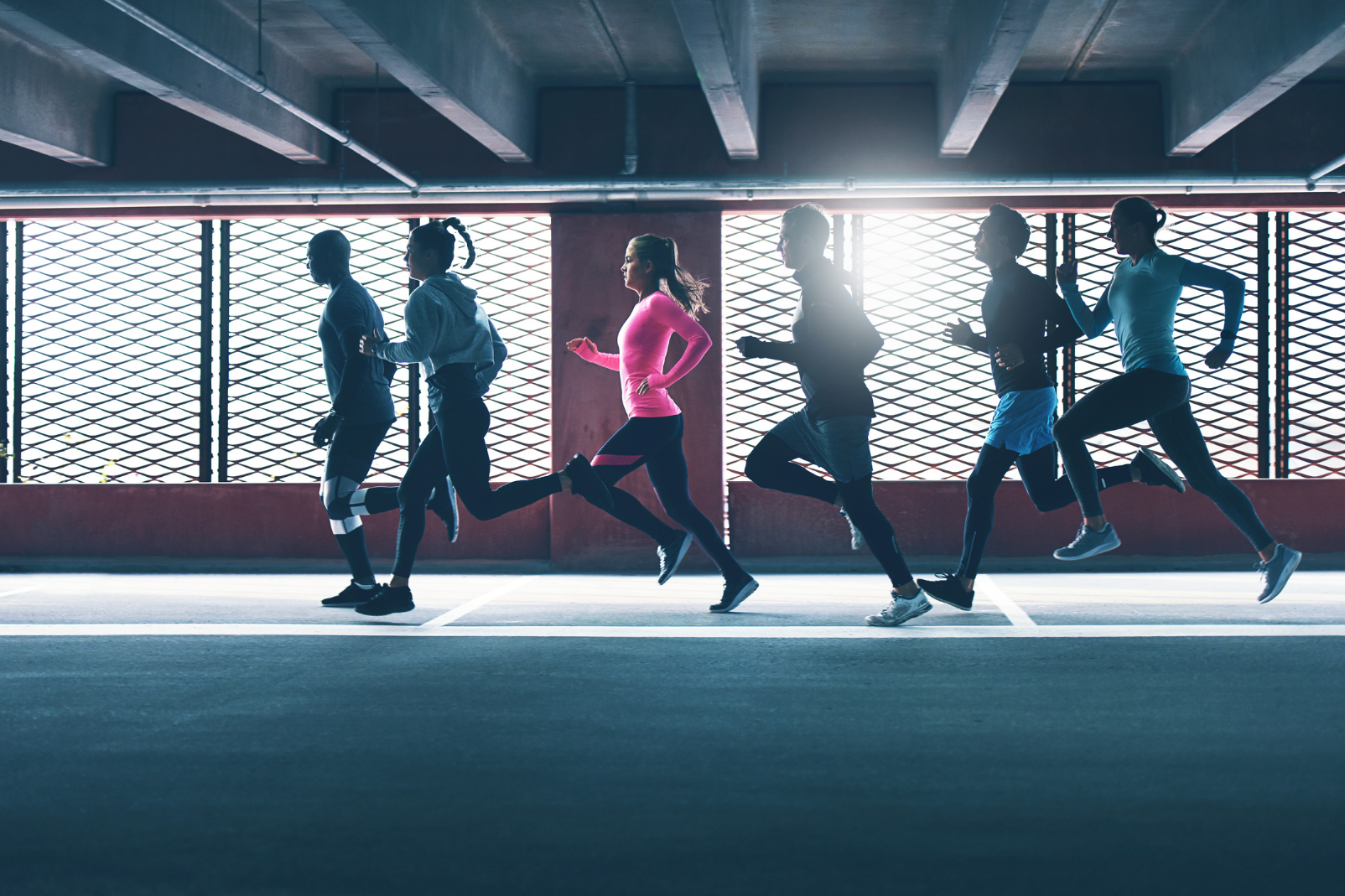 A group of runners running in a dim lit underground basement
