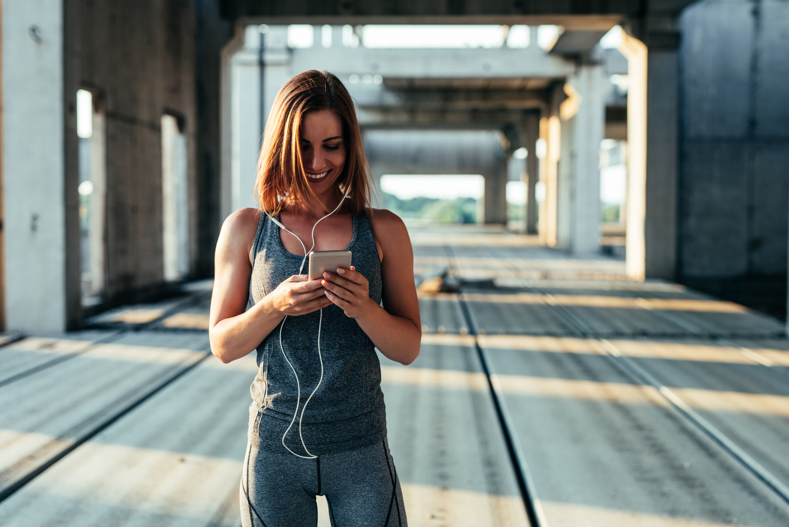 A happy woman in gym clothing, smiling and looking at her phone while standing on a wide bridge