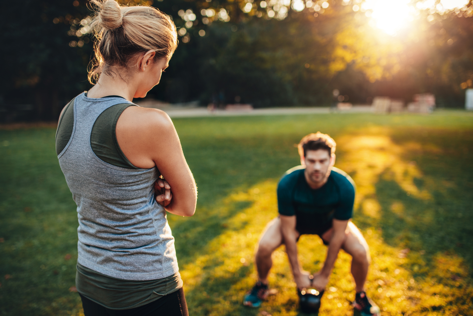 A female fitness trainer overseeing a male student as he swings a kettle-ball in an open park