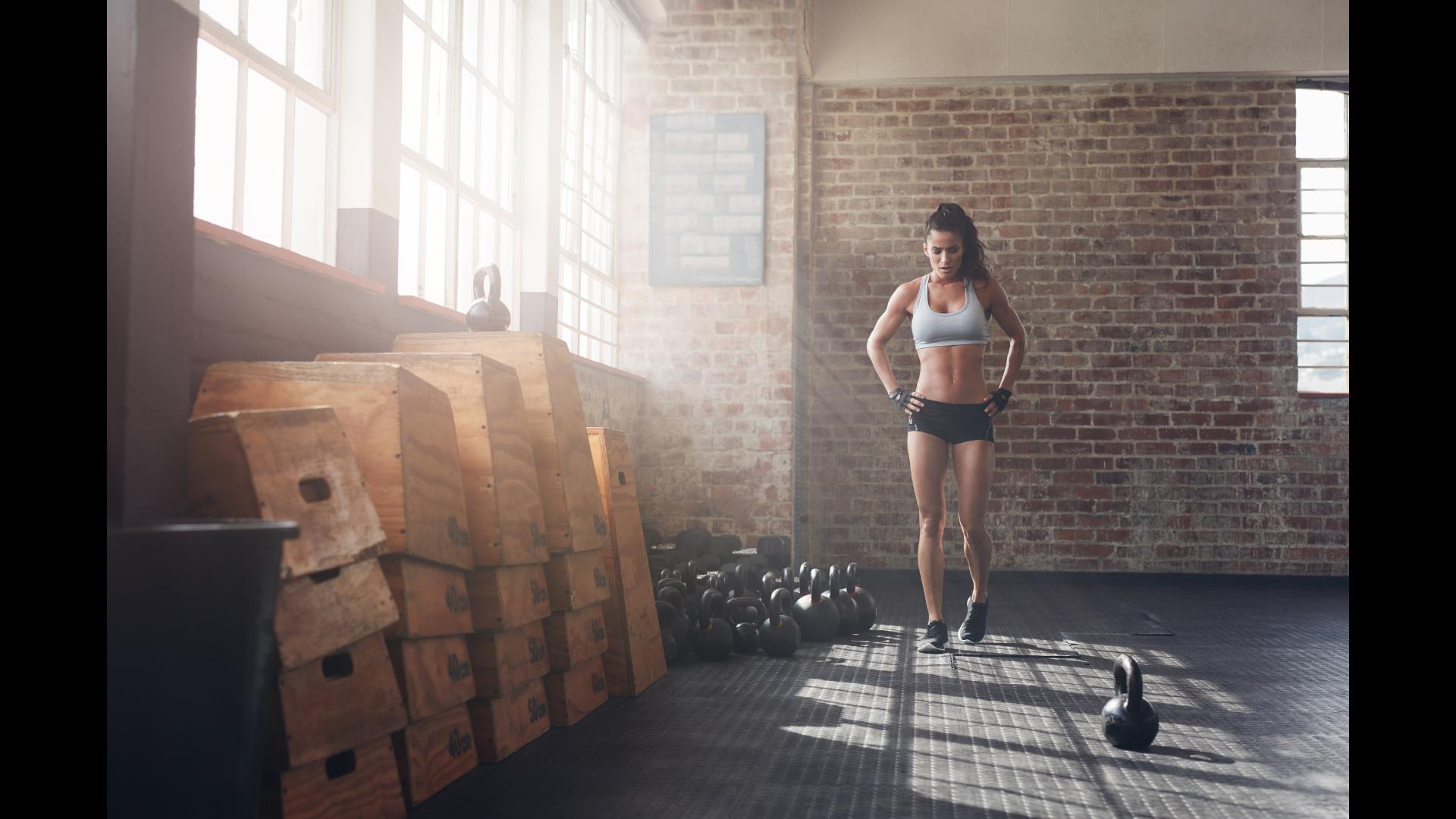 Athletic female standing besides several kettle balls