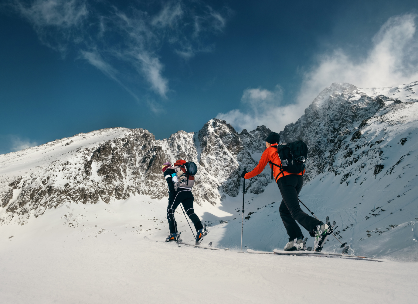 Two women skiing before huge mountains.